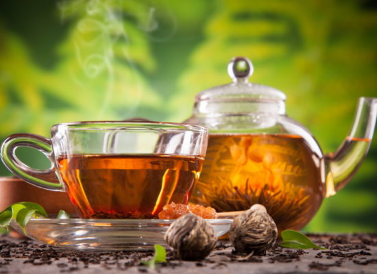 Cup of tea and teapot with blooming tea on blur green background